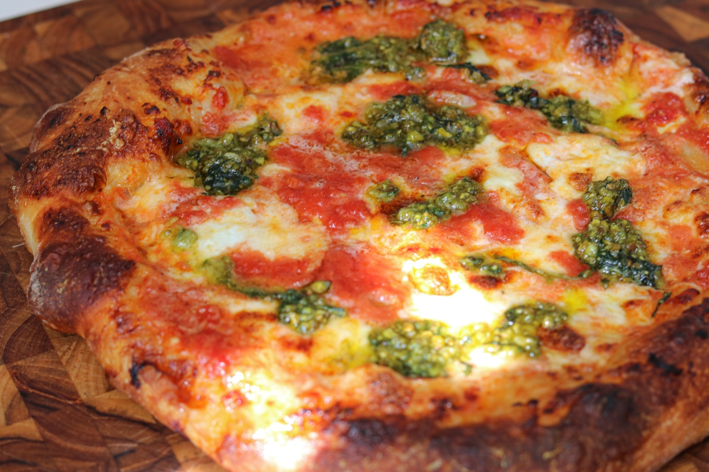 Sourdough pizza with cheese, tomato sauce and pesto